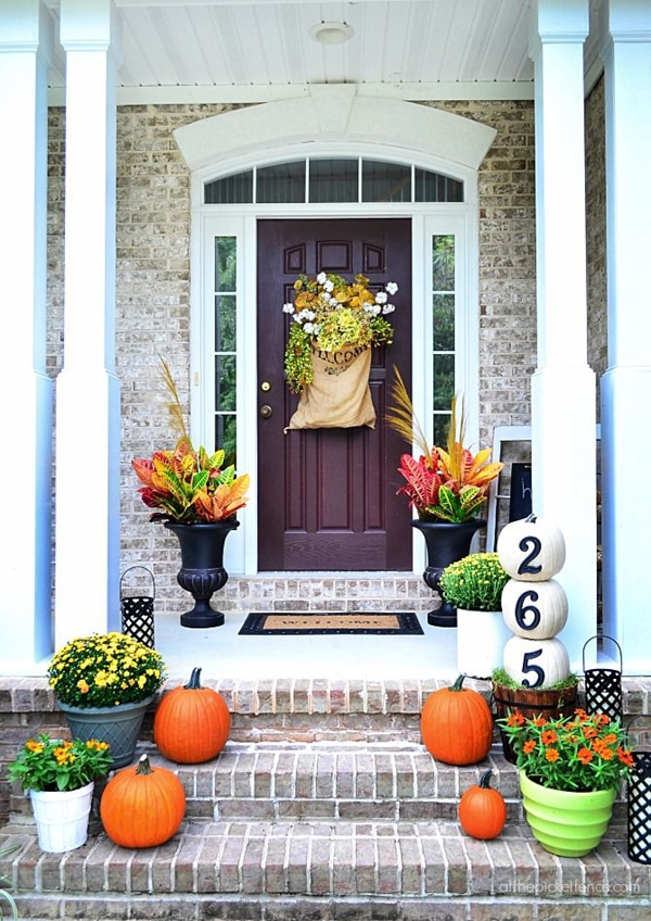 10 Fall Front Porch Decorating Ideas by A Blissful Nest - This front porch fall decor uses bright colors and creative pumpkins with house numbers to create a welcoming fall porch display.