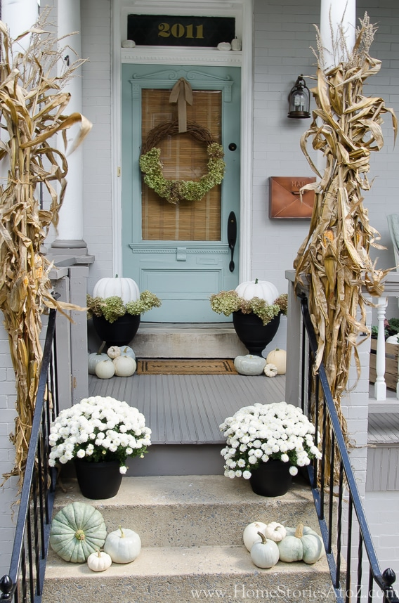 10 Fall Front Porch Decorating Ideas by A Blissful Nest - This front porch fall decor looks fresh and colorful with the pale blue door and matching pumpkin accents.