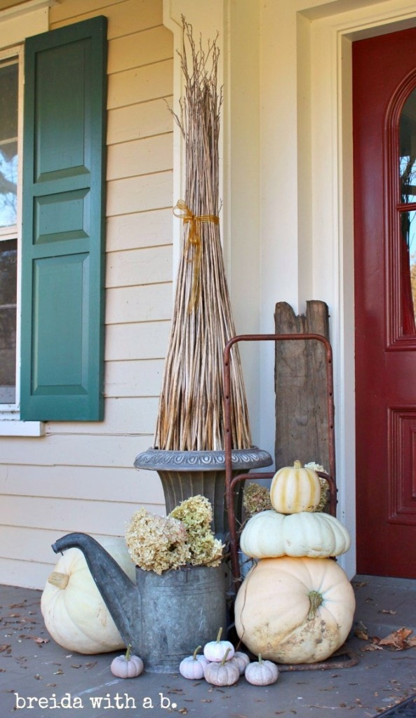 10 Fall Front Porch Decorating Ideas by A Blissful Nest - This front porch fall decor is so subtle and simplistic but still makes a beautiful statement with pumpkins and neutral colored flowers paired with that beautiful red door.