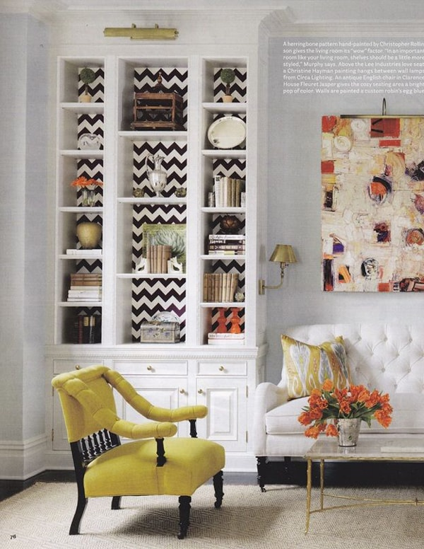 A beautifully styled bookcase with black and white striped wallpaper and vases, books, decorative plates and trinkets.