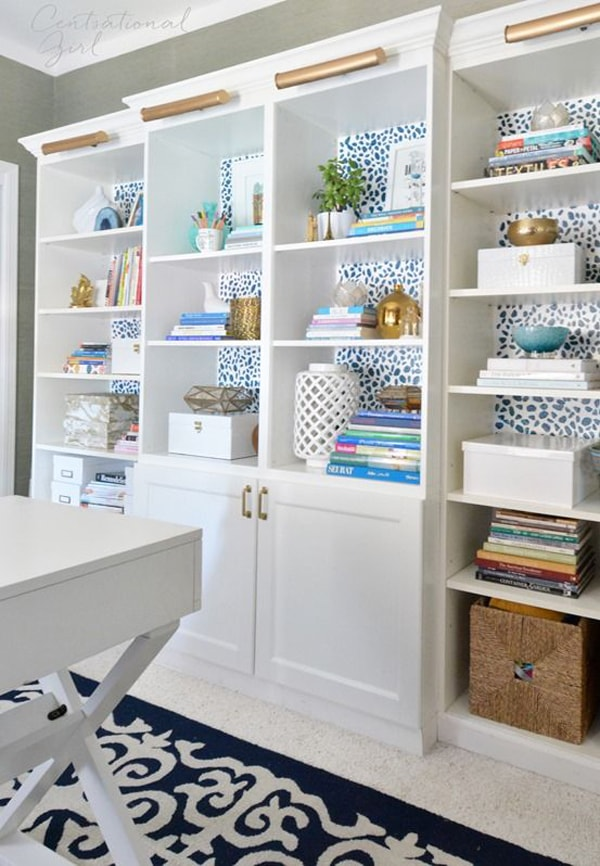 A white wooden built-in bookcase with a blue polka-dotted wallpaper background styled with accessories like books, storage containers, vaese, pictures and artwork