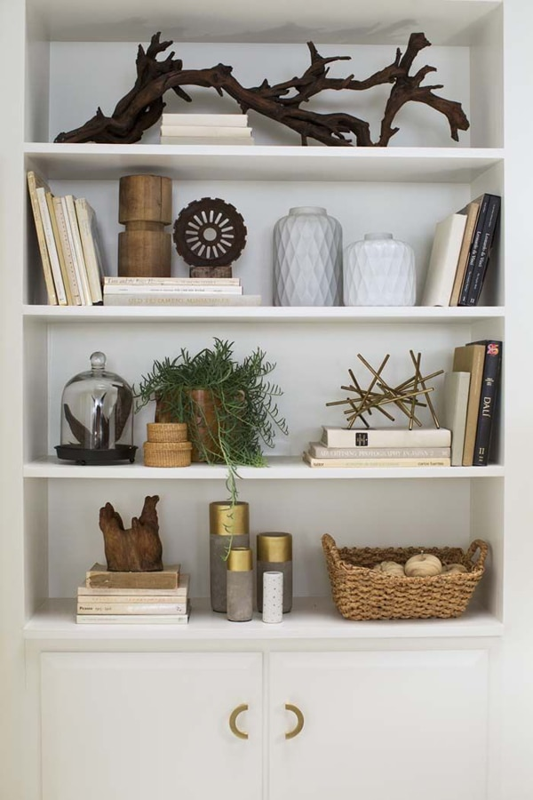 A bookcase styled with natural elements like decorative driftwood and woven baskets, stick sculptures, and plants.
