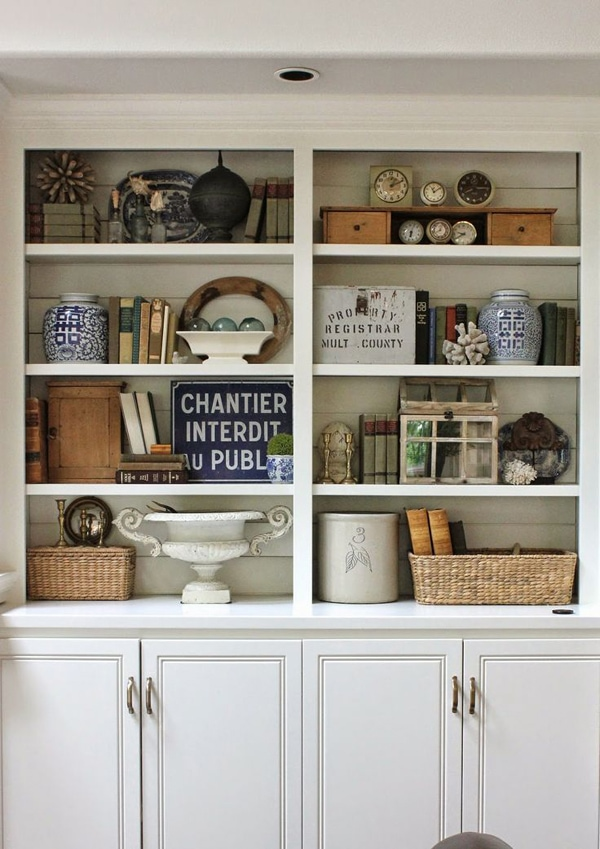 White wooden bookcase styled with collections of unique items like books, vintage vases and pedestals, woven baskets and books.