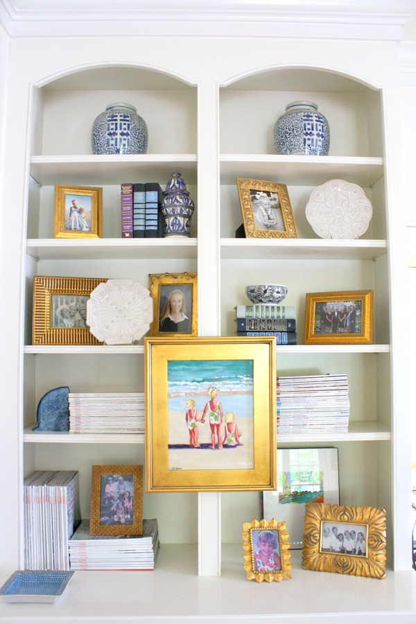 This beautiful bookcase is styled with family pictures with matching gold colored frames and stacks of magazines