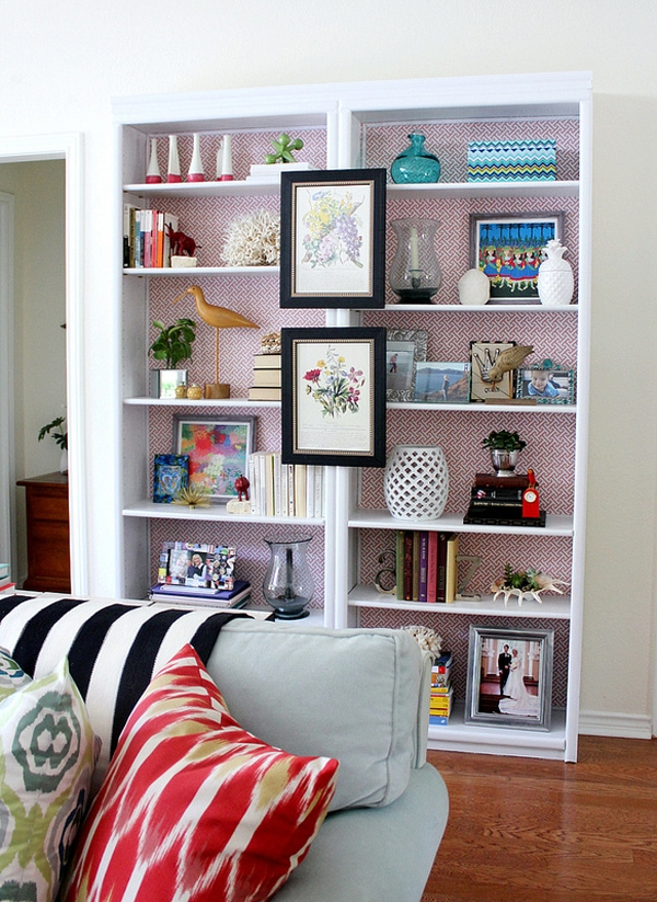 White double bookcase styled with artwork and collectables with a red and white patterned wallpaper background