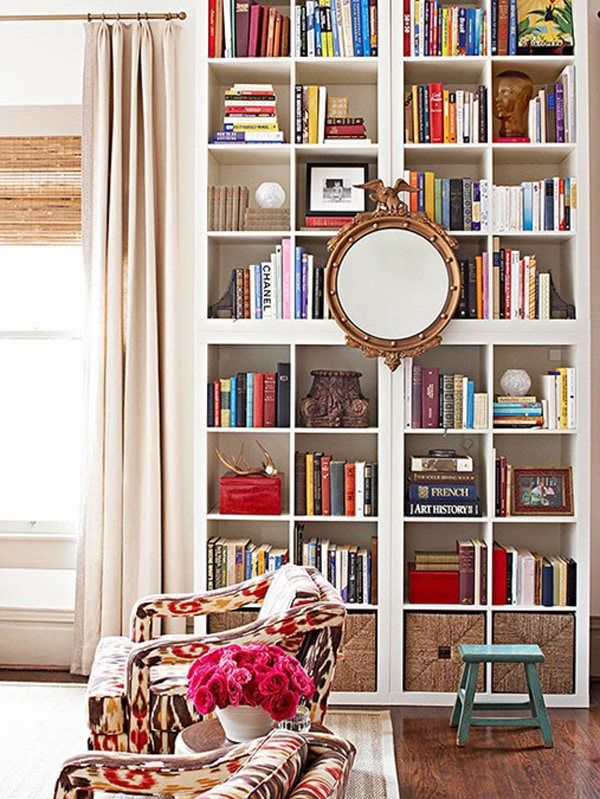 A white wooden bookcase with cube shelves, styled with a mirror in the center and filled with colorful stacks of books