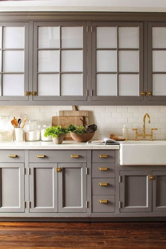 This kitchen is neutral, yet comforting with the dark grey cabinets and shiny gold hardware. The white backsplash lightens everything up.
