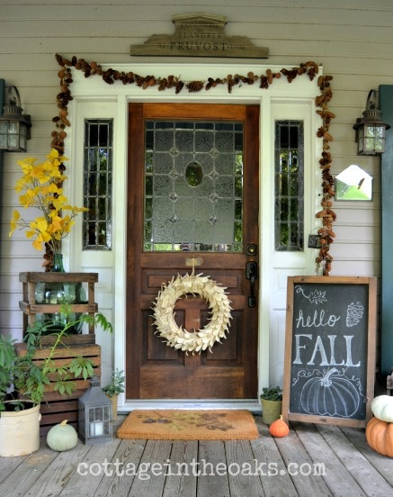 Acorn garland and a cute chalkboard complete this subtle fall porch design. #falldecor #falldecorating #fallporch