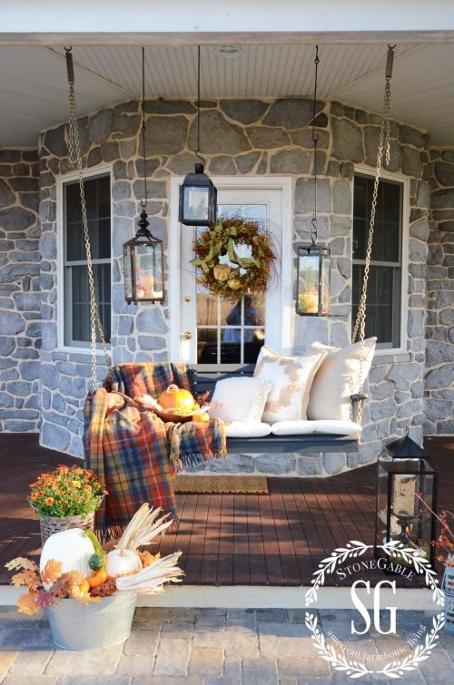All that's missing from this cozy and colorful front porch is a cup of hot chocolate and a good book! #falldecorating #fallporch #falldecor
