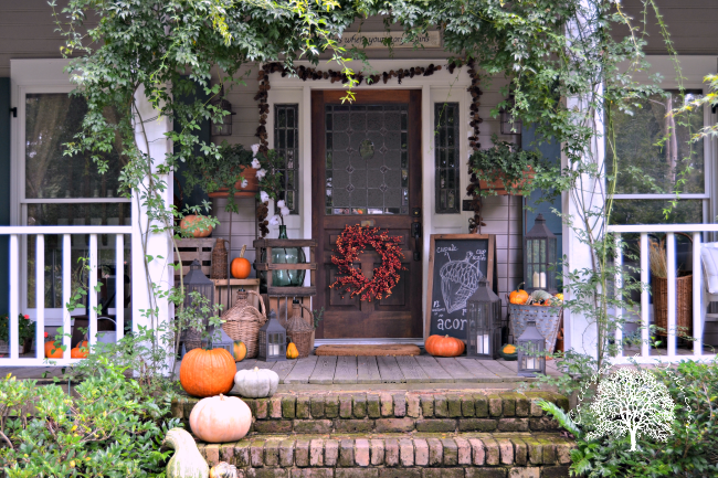 This cottage-inspired front porch looks like a perfect wooded get-away; so many bright and fresh colors. #fallporch #falldecor #falldecorating