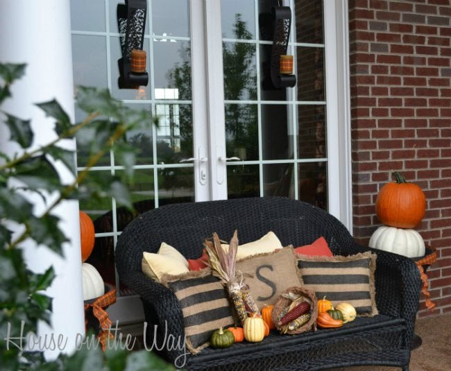 This simple porch is colorful and fall-esque with mini-pumpkins and rustic burlap fabrics. #fallporch #fallideas #falldecorating