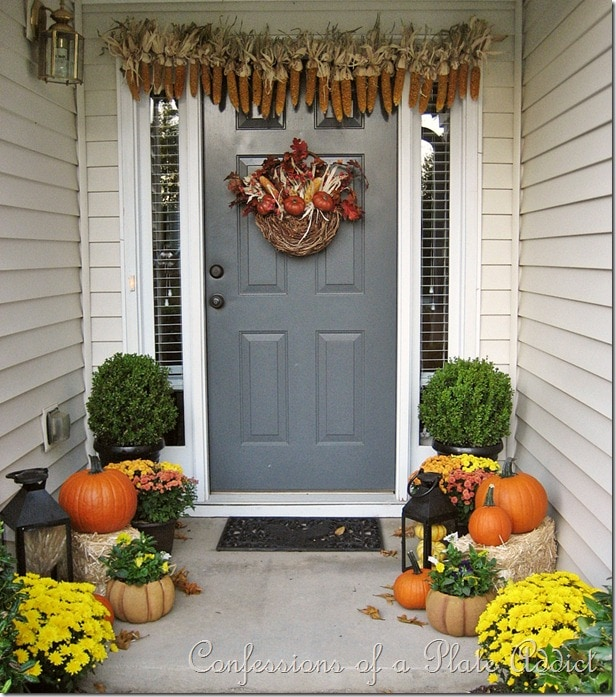 A creative way to use corn cobs! Love these colors and the balance between the two sides of the porch. #falldecor #falldecorating #fallporch