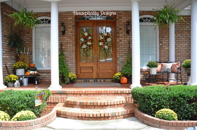 This porch has fresh flowers and fall colors that perfectly complement the still-green landscaping. #falldecor #fallporch #fallfrontporch