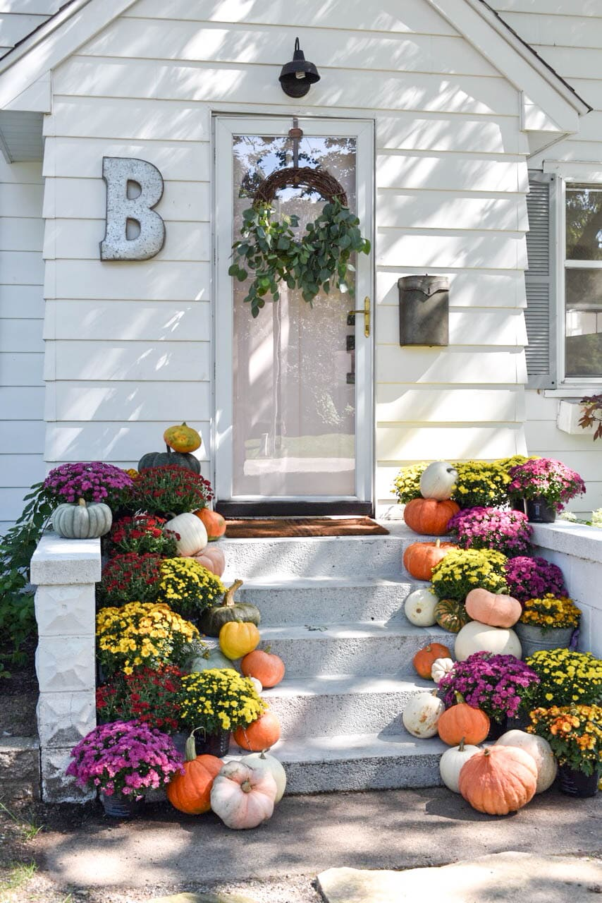 Colorful pumpkins welcome fall on this beautiful porch!