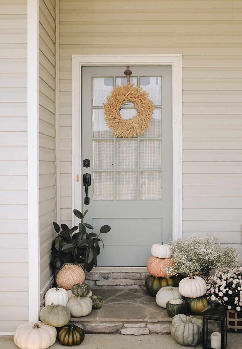 Soft muted colors for this fall front porch with pops of soft green.