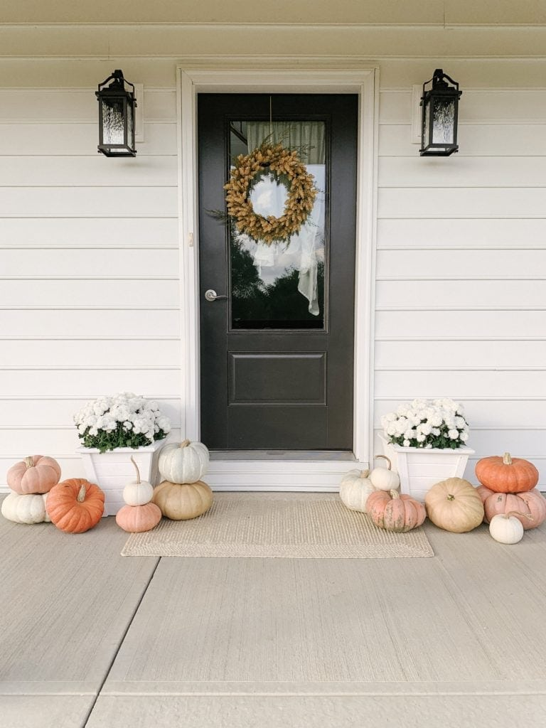 Clean and classic fall front porch with pumpkins and a wheat wreath.