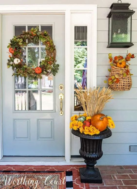 Cluster of pumpkins in urn, fall wreath in classic autumn colors.