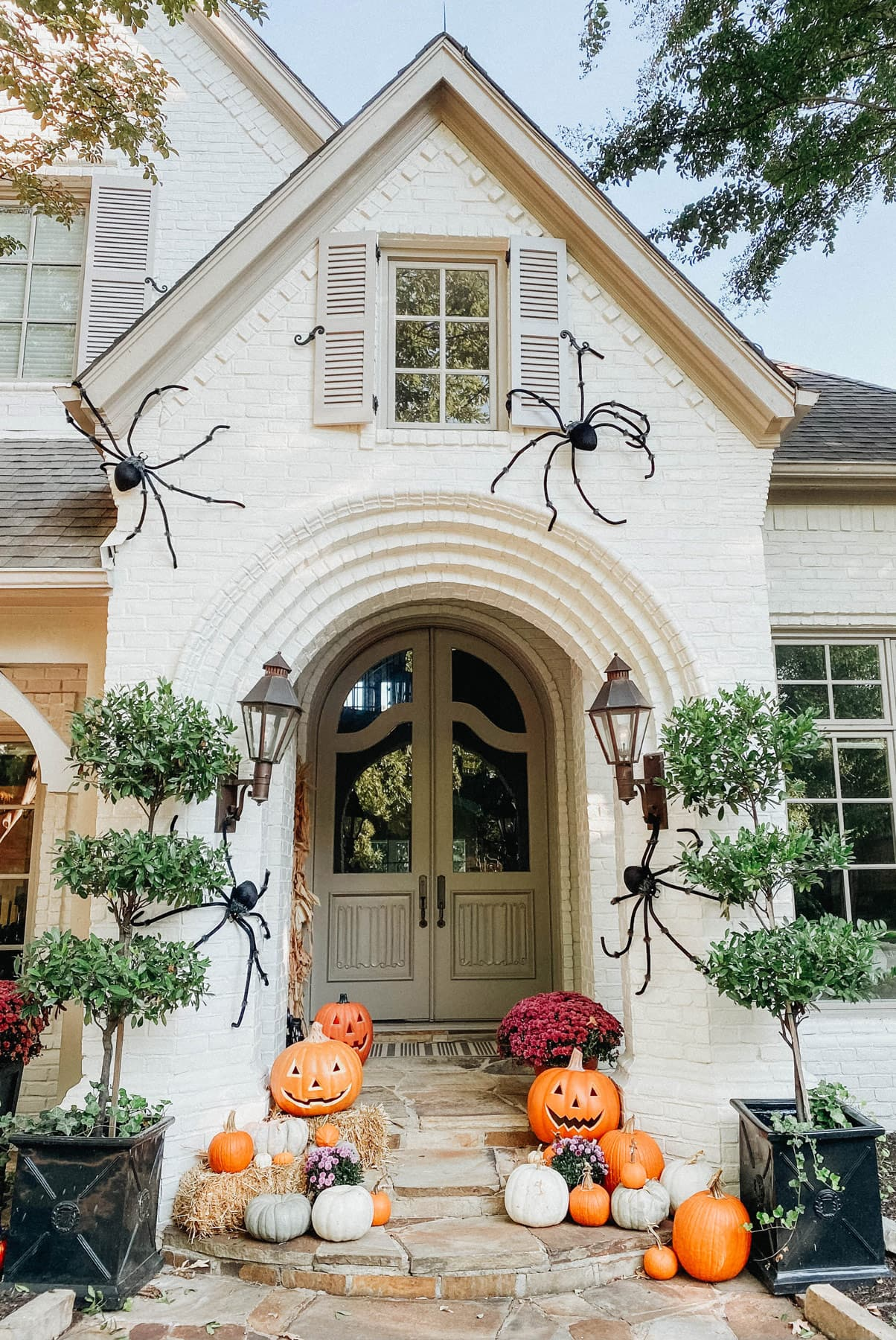 Pumpkins clustered up a walkway of a front porch with spiders.