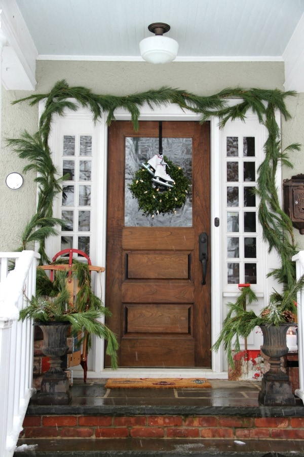 Eclectically Vintage Christmas Tree, Fresh Garland, Sled, ice skates wreath - Christmas porch ideas from A Blissful Nest