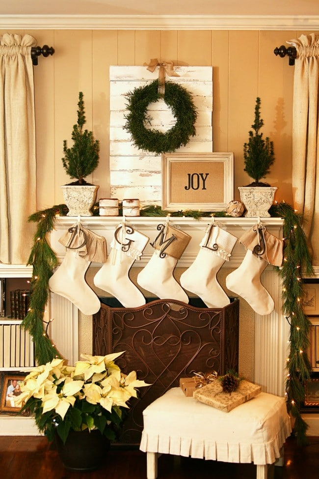 Christmas mantels - yellow, gold, white, and cream color scheme with poinsettia plant and pine wreath - Christmas Mantels - The Butlers