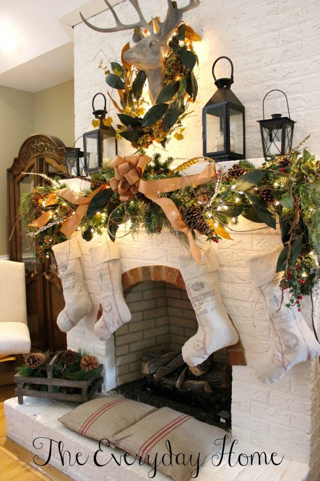 Christmas mantels - rustic country style fireplace with gold and green wreaths, deer head, burlap ribbons - Christmas Mantel The Everyday Home