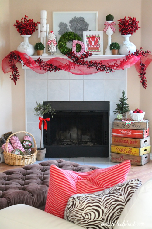Christmas Mantels - white tile with red holly berry garland, red and green flower accents and red ribbon - Our Christmas Mantel A Blissful Nest