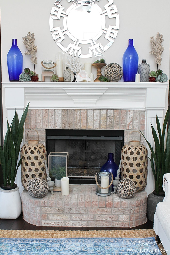 If you love the coastal look then this one is for you! Touches of coral, blue and white and gorgeous wood textures were used to create this show stopping fireplace mantle by A Blissful Nest. See more on http://ablissfulnest.com #coastal #livingroom #blueandwhite #coastalliving #livingroomideas #fireplacemantleideas #designtips