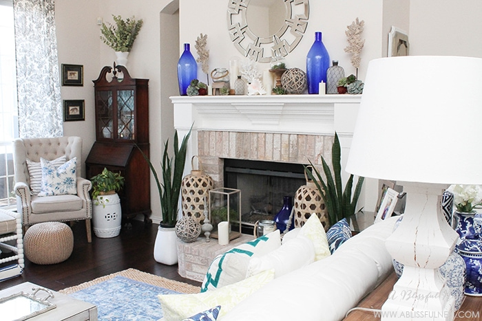 If you love the coastal look then this one is for you! Touches of coral, blue and white and gorgeous wood textures were used to create this show stopping fireplace mantle by A Blissful Nest. See more on https://ablissfulnest.com #coastal #livingroom #blueandwhite #coastalliving #livingroomideas #fireplacemantleideas #designtips