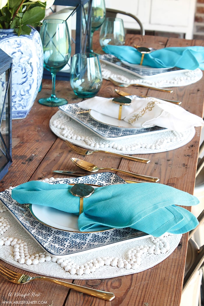 Fresh coastal table décor ideas for the perfect summer night. Grab these tips on setting the perfect coastal tablescape by A Blissful Nest. https://ablissfulnest.com/ #coastal #tabledecor #tabledecorideas #coastalinteriors #coastalroom #ocean #blueandwhite