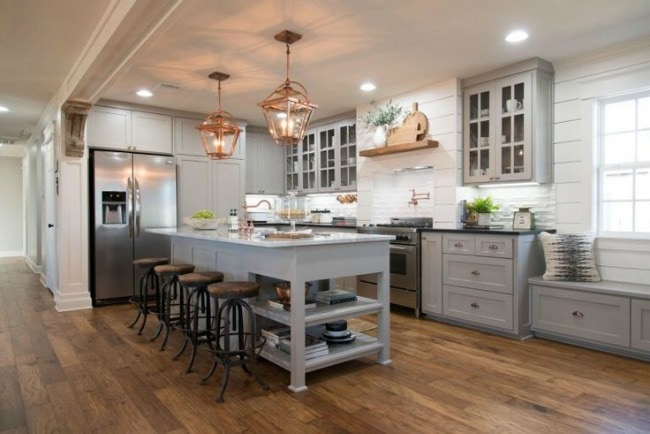 The copper and mixed metal accents in this kitchen give it a rustic, industrial vibe, but the cute farmhouse window seating and gorgeous gray cabinet colors bring it all together! Mangolia Market The Carriage House, 20 Best Fixer Upper Rooms