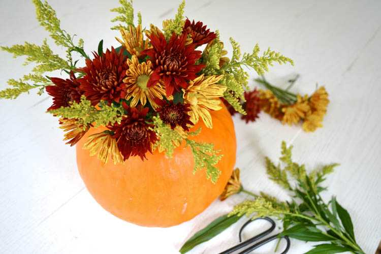 A super cute and simple DIY pumpkin centerpiece idea perfect for a fall table or Thanksgiving table idea! See more on https://ablissfulnest.com/ #falltable #pumpkinideas #falldecor