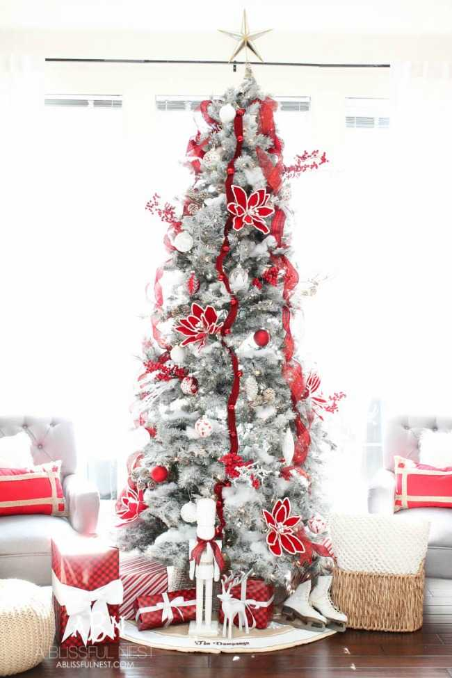 This festive, sparkling white, silver, and red Christmas tree is accented with snowy poinsettia flowers and red ribbon, topped with a simple golden star