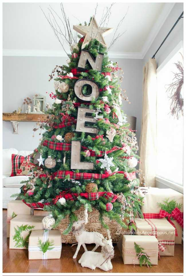A rustic winter wonderland NOEL tree that's accented with Christmas themed plaid ribbon and presents with wisps of evergreen