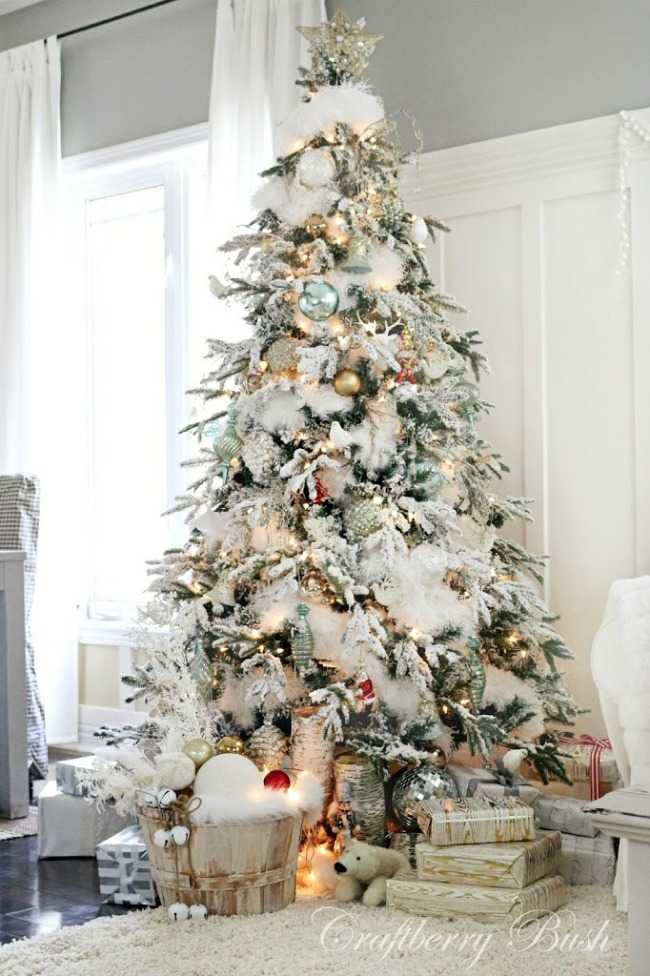 White fur garland gives this Christmas tree it's snow dusted look. Accents of gold make the tree pop with light