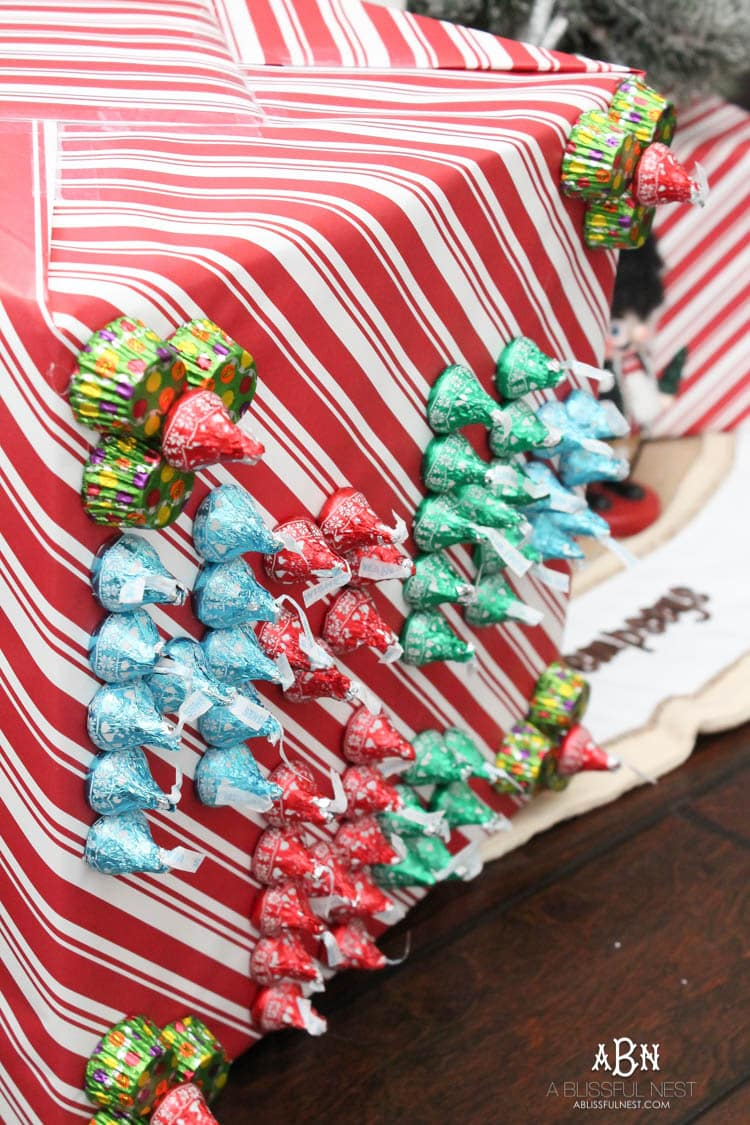 Wrap your presents in chocolaty goodness with Hershey's Kisses! This is such a fun and unique idea to decorate a gift. Then they can eat the candy later after the present has been opened! So fun! See more on https://ablissfulnest.com/ #hersheyskiss #christmascraft #christmasdiyidea