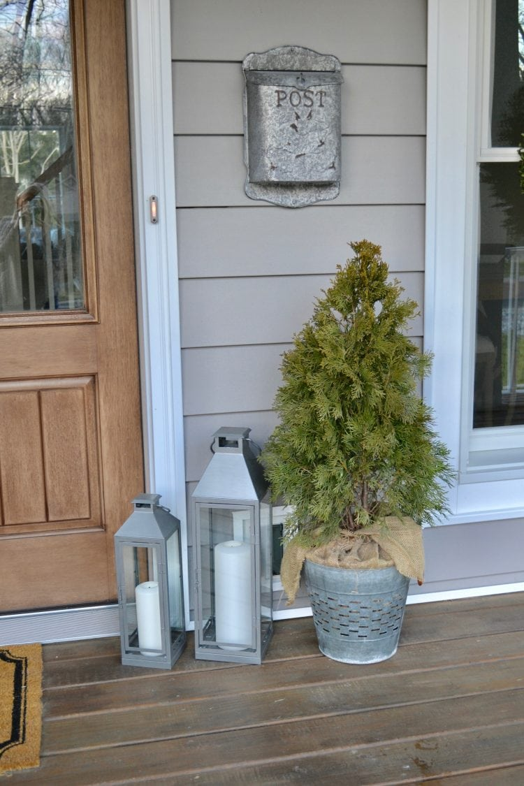 These simple porch decorations are the easiest way to refresh your home in the new year. Silver lanterns with a mini spruce bushell really complete the look!