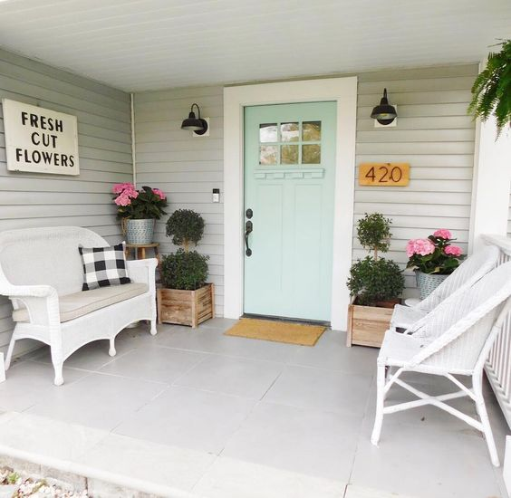 "Love the fresh colors of this spring front porch! This porch has a mint green painted front door. On either side, wooden planter boxes hold green shrubs and bright pink flowers. Wicker porch furniture is decorated with black and white flannel throw pillows. A wooden sign hanging on the wall says ""fresh cut flowers"". #spring #springporch #springdecorating #springfrontporch"