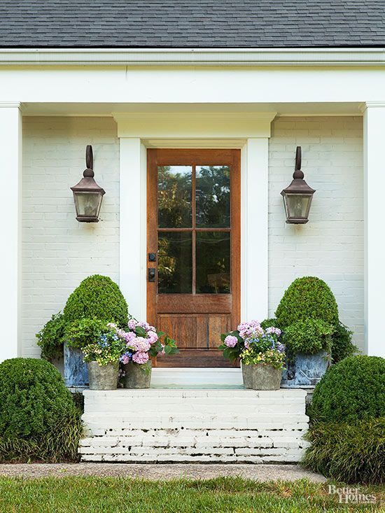 Add lots of potted plants to your front porch for spring. Love this beautiful spring front porch. #spring #springporch #springdecorating #springfrontporch
