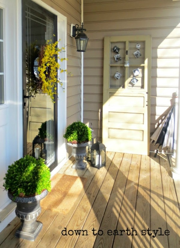 Spring front porch with stone planters filled with green shrubbery. A weathered wood door decorated with vintage photographs leans against the wall. On the door, there is a twig wreath with bright yellow flowers. Gray metal lanterns flank the planters.