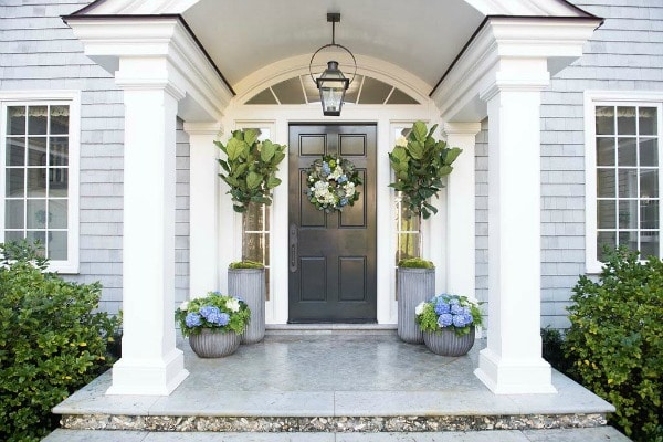This spring themed front porch is decorated with large planters filled with spring floral arrangements. Two planters flank the door holding fig leaf plants. A white, blue, and green wreath adorns the front door. This color scheme is matched in the smaller, round planters on either side of the porch.