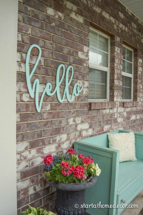 A light turquoise hello sign hangs on the brick wall. This porch has a stone planter with pink and purple flowers. A cute wooden bench is painted turquoise blue and decorated with a frilly white throw pillow.