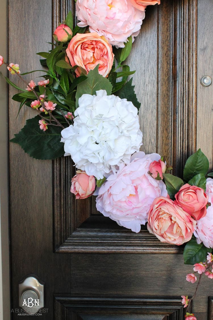 Adding pop of pinks a a DIY wreath makes this spring porch pop! #springporch #springfrontporch #springdecorating #springdecoratingideas