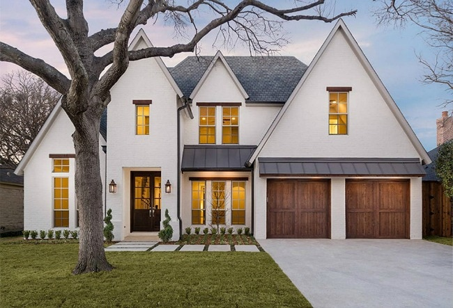 This white exterior pops with these contrasting wood garage doors. #whitehome #exteriorpaint #whitepaint