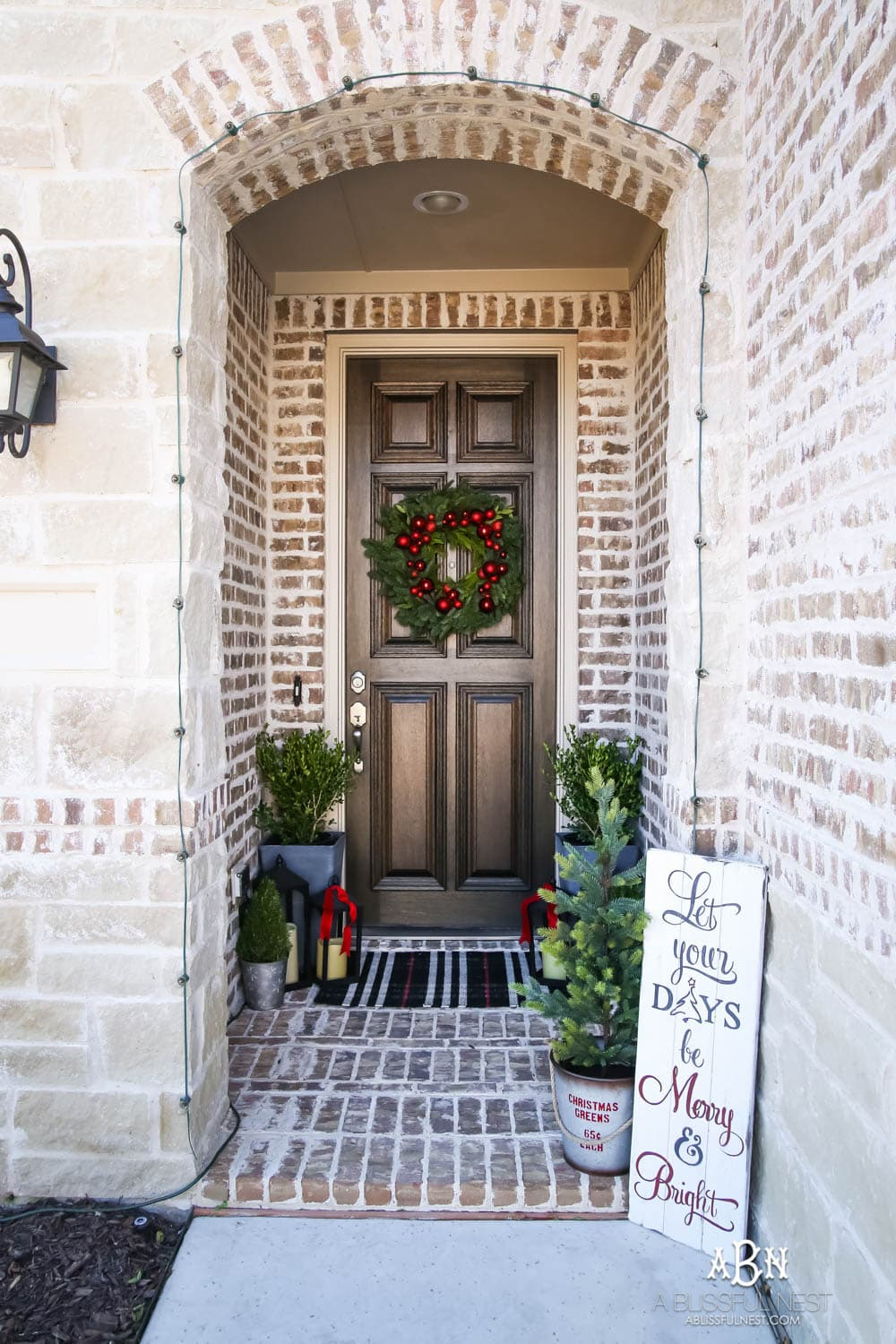 Classic Christmas front porch with red, white and black details. Festive plaid door mat and simple black lanterns. Red Christmas balls on a beautiful Christmas wreath. #christmasporch #christmasfrontporch #christmasporchdecor #christmasporchideas #christmashometour