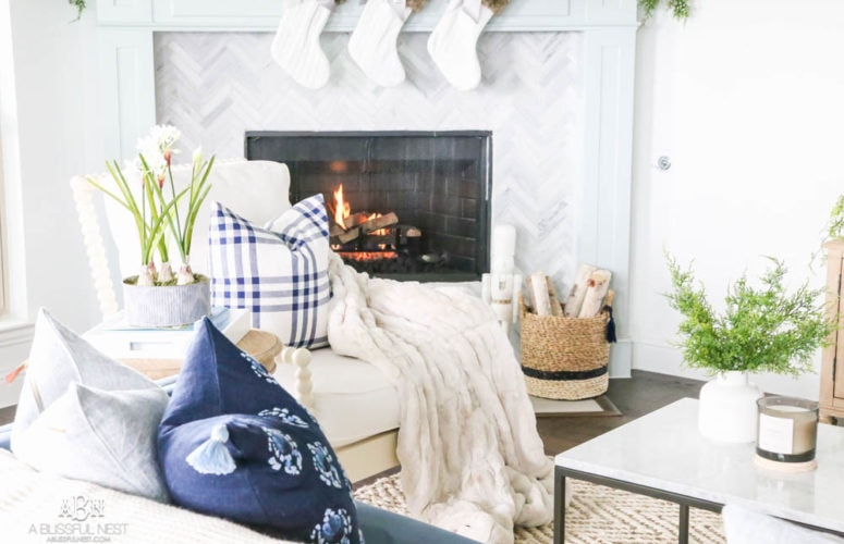 Beautiful blue and silver Christmas living room decor in a bright white space with juniper garland and silver and blush ornaments. Check out all the white, silver and gold Christmas decor in this holiday home tour on ABlissfulNest.com. #ABlissfulNest #Christmasdecor #Christmasdecorating #CoastalChristmasdecor