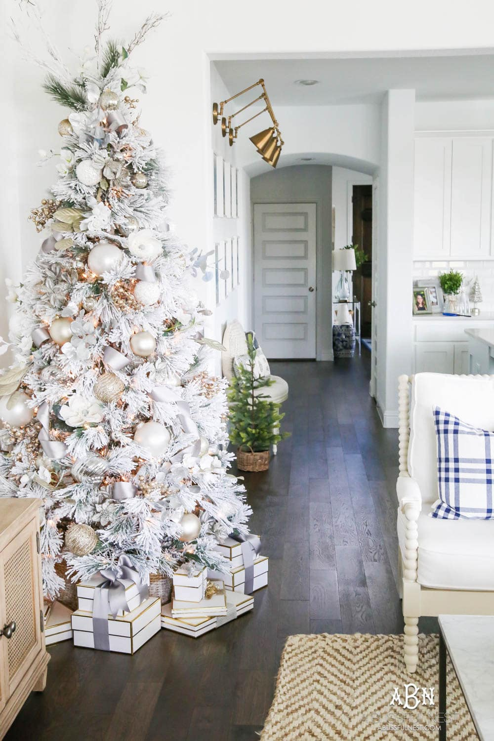 Silver and gold Christmas tree in an open concept floor plan with lots of blue home decor accents. Check out all the white, silver and gold Christmas decor in this holiday home tour on ABlissfulNest.com. #ABlissfulNest #Christmasdecor #Christmasdecorating #CoastalChristmasdecor