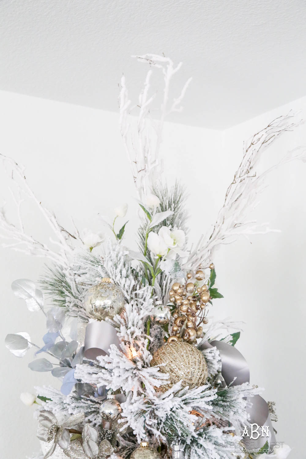 Silver and gold Christmas tree in an open concept floor plan with lots of blue home decor accents. Check out all the white, silver and gold Christmas decor in this holiday home tour on ABlissfulNest.com. #ABlissfulNest #Christmasdecor #Christmasdecorating #CoastalChristmasdecor #christmastree