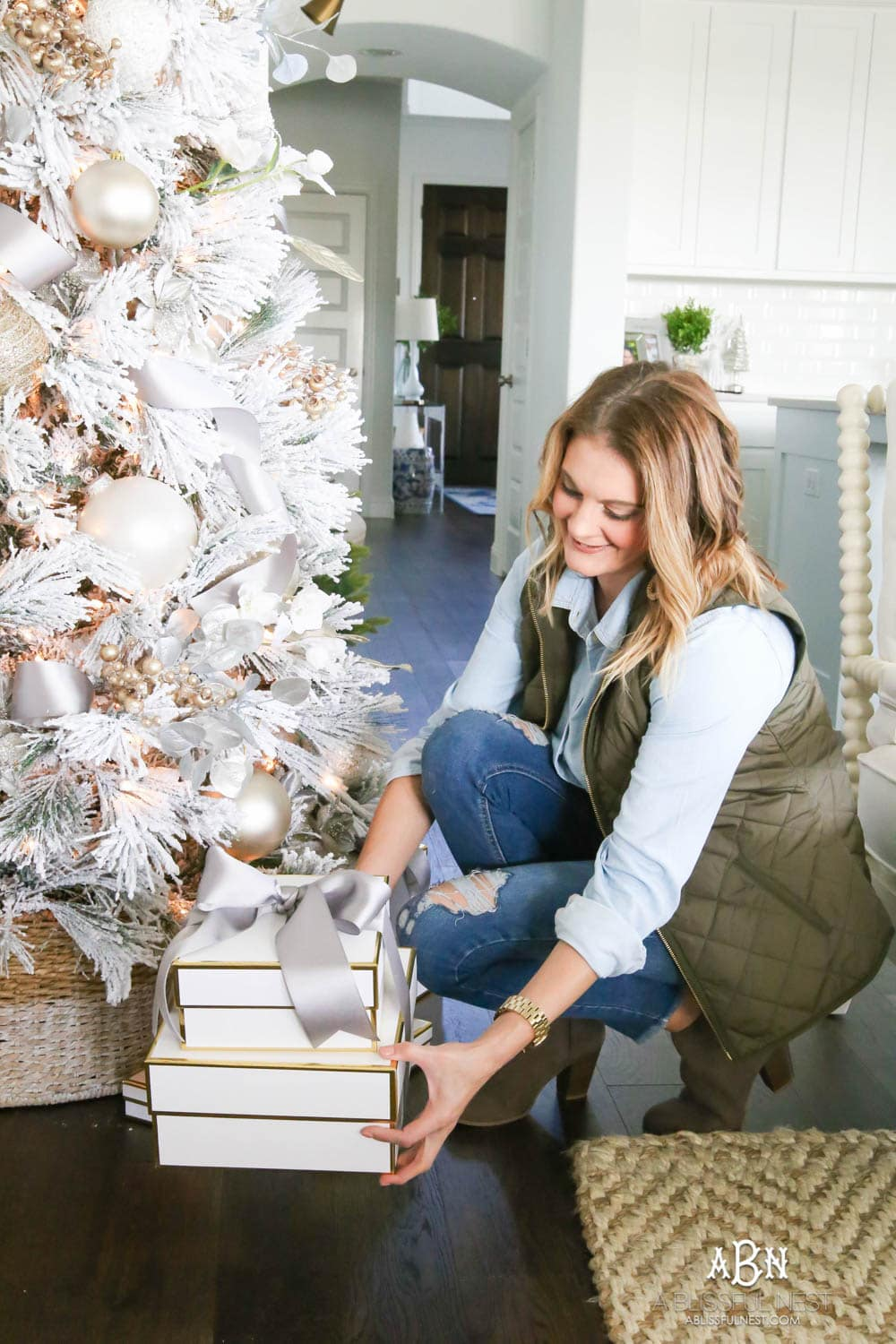 White boxes with gold trim make the perfect wrapping for gifts under this white flocked tree with silver and gold accents. Check out all the white, silver and gold Christmas decor in this holiday home tour on ABlissfulNest.com. #ABlissfulNest #Christmasdecor #Christmasdecorating #CoastalChristmasdecor #christmastree