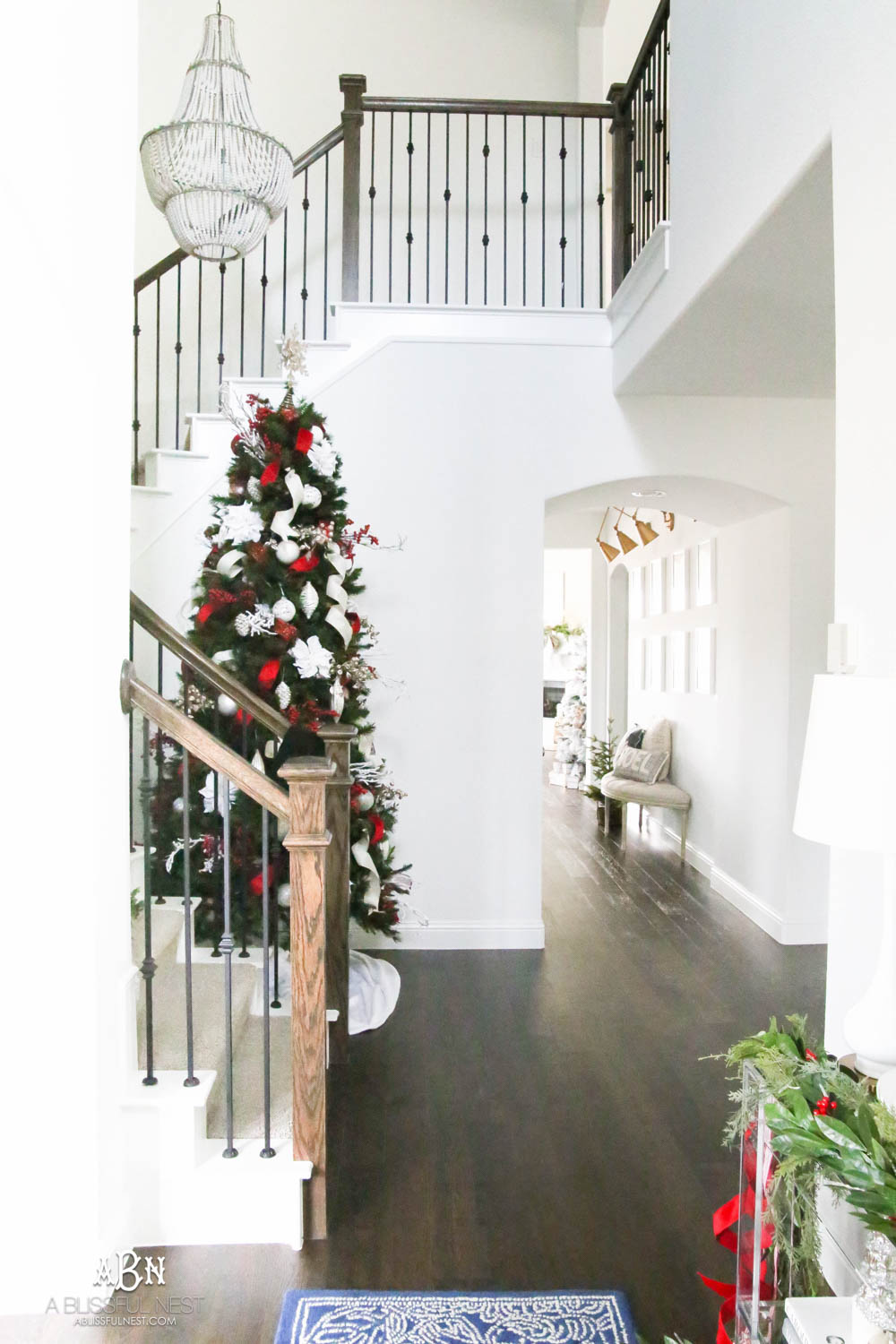 Simple classic Christmas tree and holiday entryway with red and white holiday décor. Christmas tree in stairway with all white walls. #christmasentryway #christmasentry #christmasentrydecor #christmasentrywayideas #christmashometour