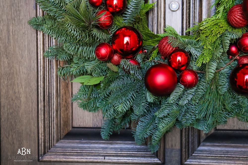 Classic Christmas front porch with red, white and black details. Festive plaid door mat and simple black lanterns. Red Christmas balls on a beautiful Christmas wreath. #christmasporch #christmasfrontporch #christmasporchdecor #christmasporchideas #christmashometou